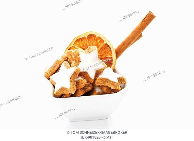 Cinnamon star-shaped biscuits with cinnamon and dried orange slices in a bowl