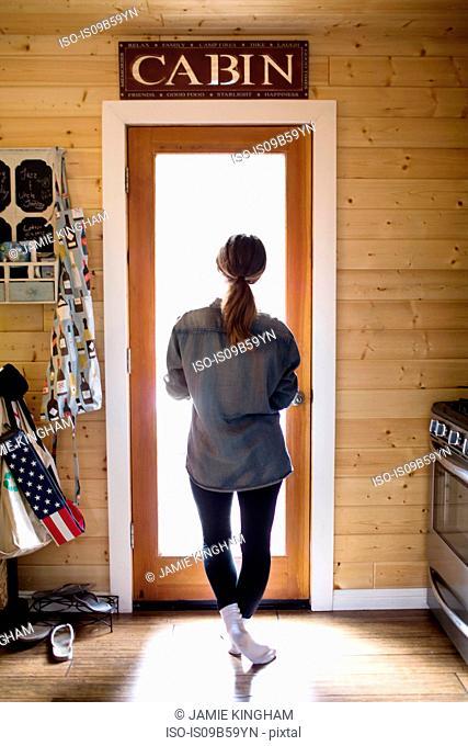 Young woman standing by doorway, looking through window