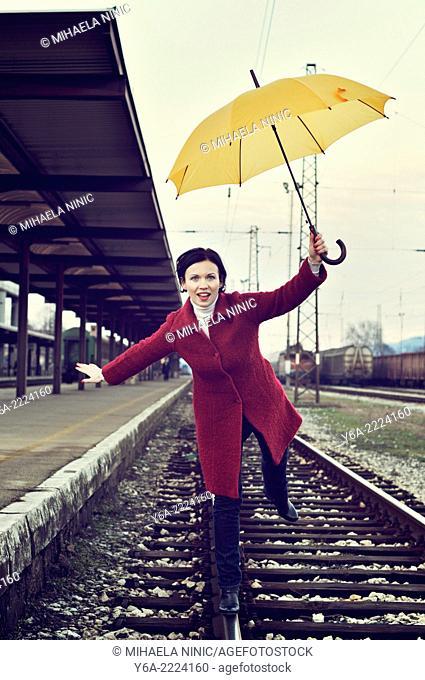 Woman balancing on one leg standing on railway track holding umbrella