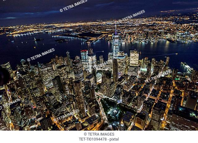 USA, New York, New York City, Manhattan, Aerial view of illuminated skyline with harbor at night