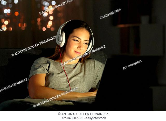 Woman watching videos online in the night sitting on a couch in the living room at home