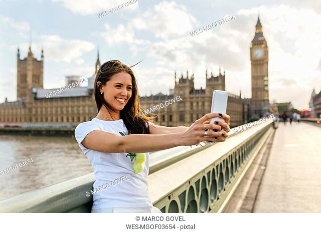 UK, London, beautiful woman taking a selfie on Westminster Bridge