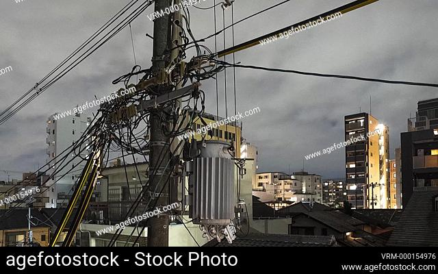 timelapse of a downtown district of Kyoto with an electric transformer in the foreground