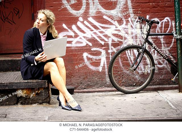 Caucassian businesswoman working on laptop sitting on a stoop on a public street