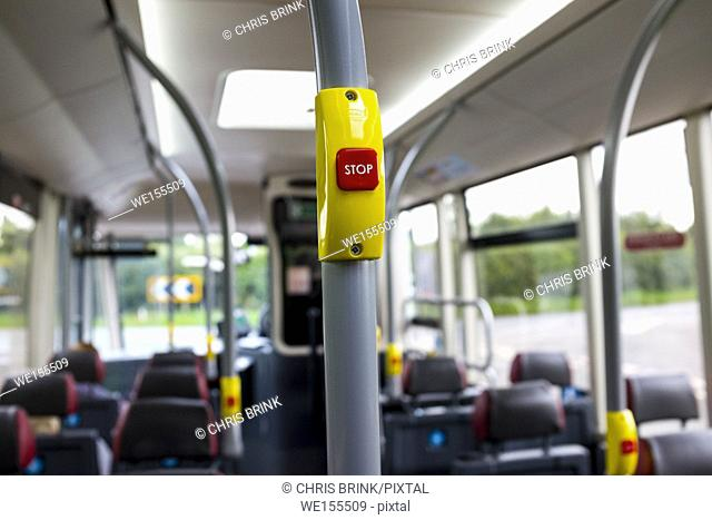 Close up of a red stop button with braille inside an English bus