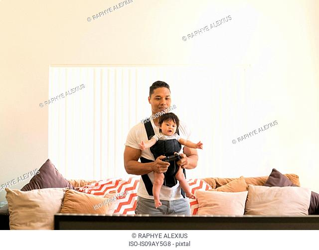 Father with baby in carrier, playing video game