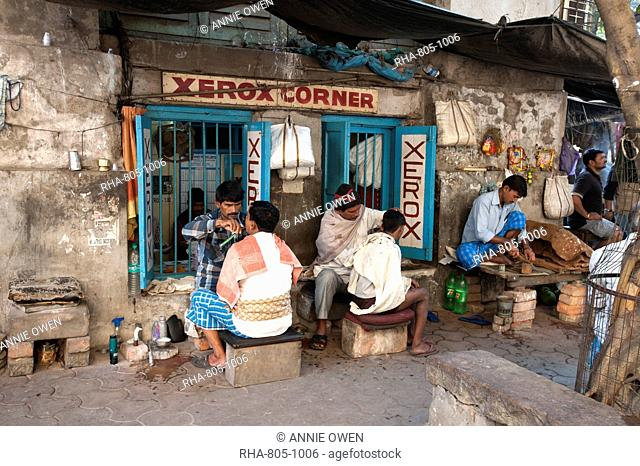 Barbers cutting hair and shaving men, and tobacco wallah, in street stalls outside Xerox shop in Dalhousie Square area of Kolkata (Calcutta), West Bengal, India