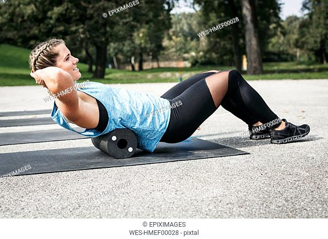 Smiling woman doing workout exercise with fascia roll outdoors