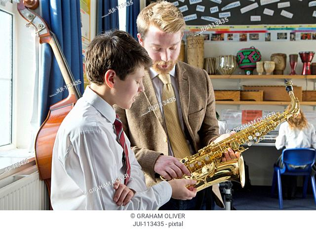 Music teacher and middle school student discussing saxophone in music class