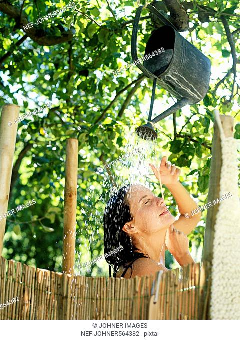 A woman taking a shower from a water jug in a garden