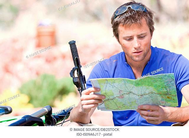 Man reading map on mountain bike