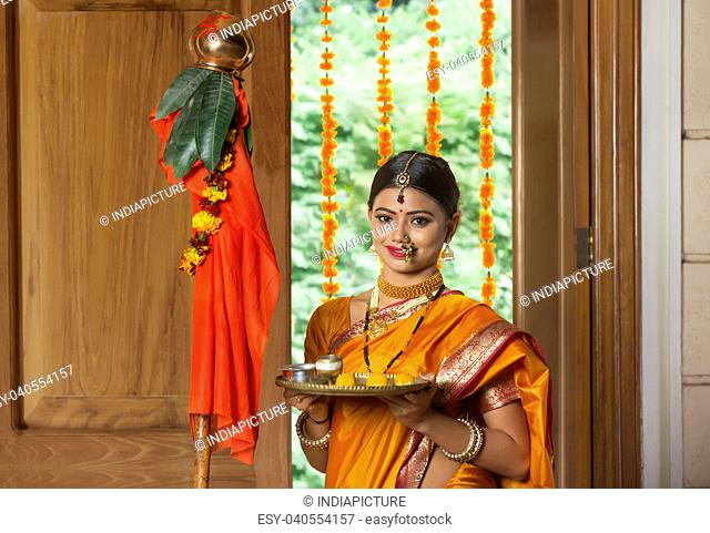 Portrait of a maharashtrian woman in traditional dress celebrating gudi padwa festival holding a pooja plate