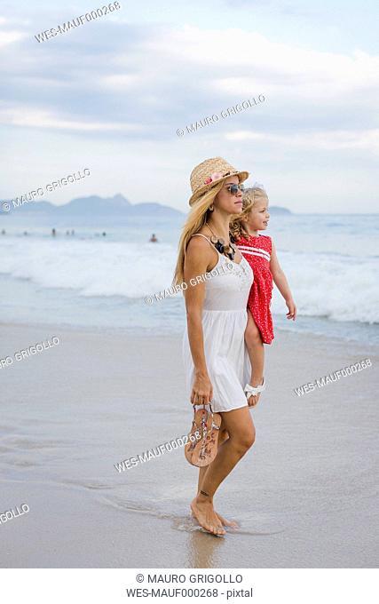 Brasil, Rio de Janeiro, mother carrying daughter on Copacabana beach