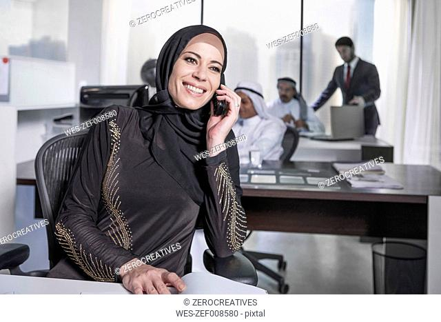 Middle Eastern businesswoman in office talking on the phone
