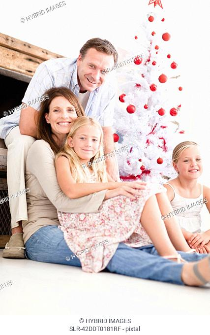 Family relaxing by Christmas tree