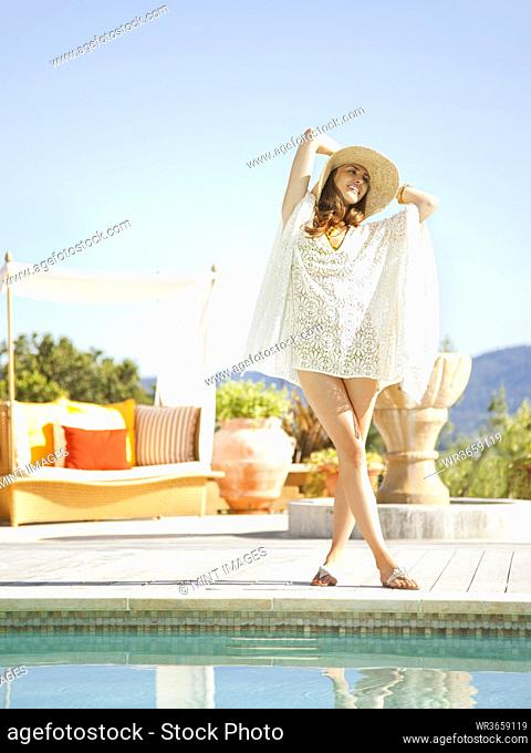 Beautiful woman standing on the edge of the pool at a luxury resort overlooking wine country in Napa Valley California