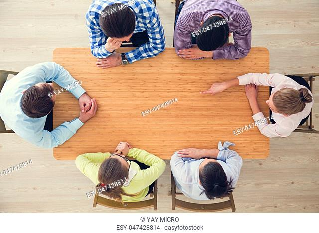 Hipster business teamwork brainstorming planning meeting concept, people team sitting around the table pointing to copy space