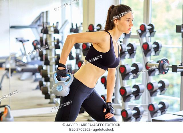 Kettlebells, Woman lifting weights at the gym