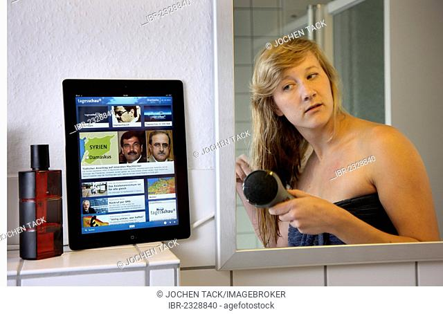 Young woman in the bathroom in the morning, blow-drying her hair and reading a news page on an iPad, tablet computer, wireless internet access