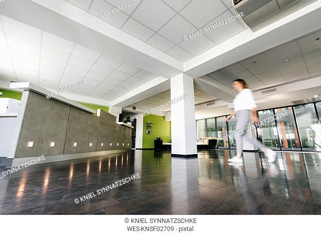Businesswoman entering reception, blurred motion