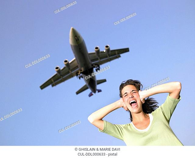 Woman covering ears and screaming with plane flying overhead