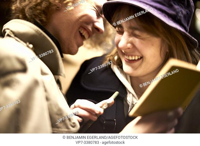 Couple looking at book, laughing. Nightlife, in Berlin, Germany