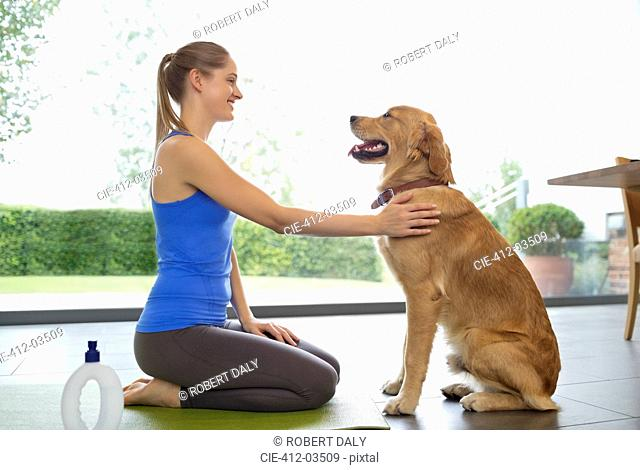 Woman practicing yoga with dog in living room