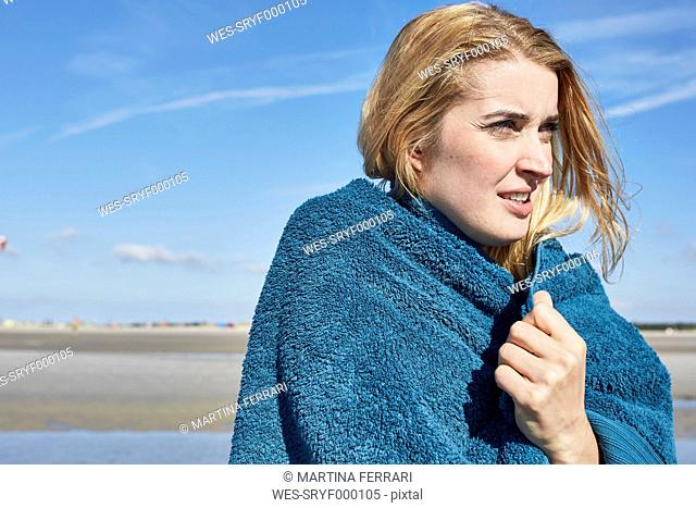 Young woman wrapped in a towel on the beach