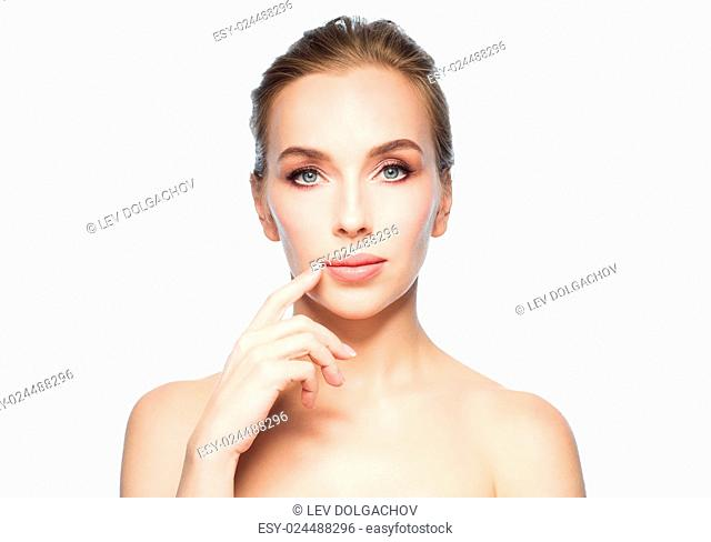 beauty, people and plastic surgery concept - beautiful young woman showing her lips over white background