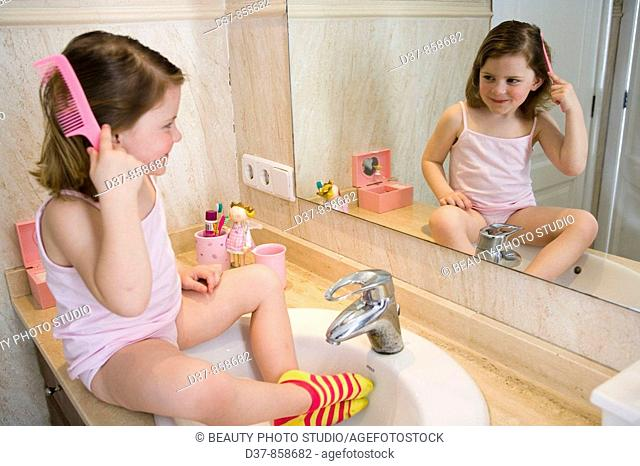 Little girl combing her hair in the bathroom