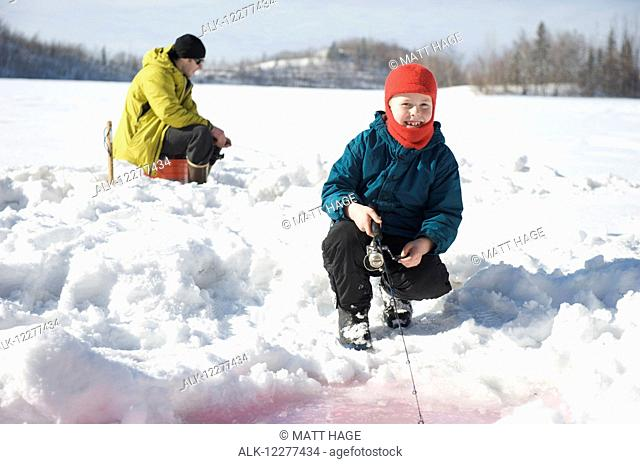 Boy ice fishing on Matanuska Lake in the Matanuska Valley north of Anchorage, Southcentral Alaska