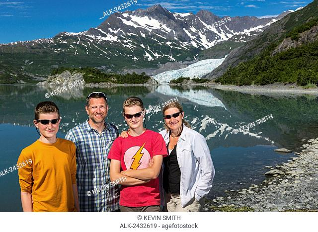 Family poses for a group picture on the beach with Shoup Glacier in the background, Shoup Bay State Marine Park, Prince William Sound, Southcentral Alaska