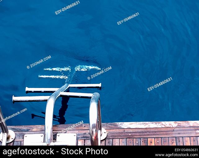 Boat Metal shiny staircase ocean on blue sea water background. Traveling destinations Red Sea vacation tourism shore summe