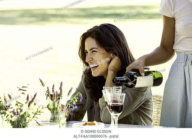 Woman enjoying meal with friend outdoors