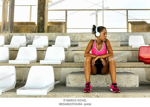 Female athlete taking a break, listening to music