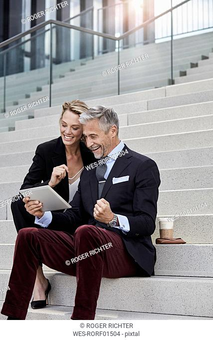 Two business people sitting together on stairs looking at tablet