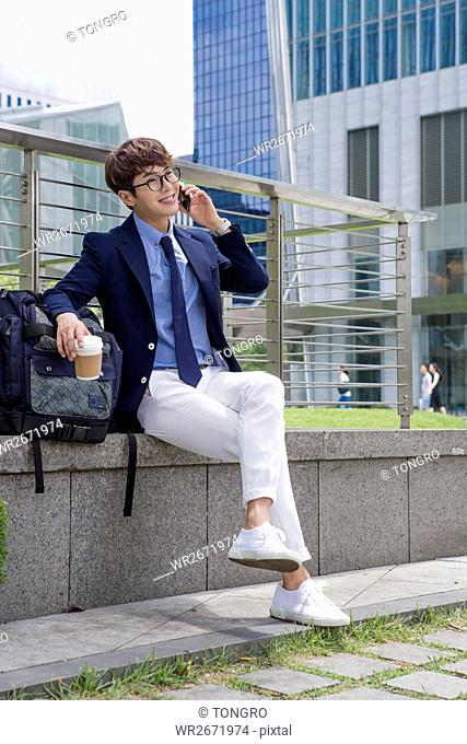 Smiling businessman sitting talking on cellphone outdoors