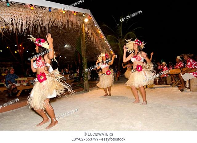 Portrait of Polynesian Pacific Island Tahitian female dancer in colorful costume dancing on tropical beach
