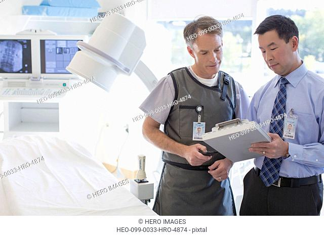 radiology technician and doctor reviewing medical chart together