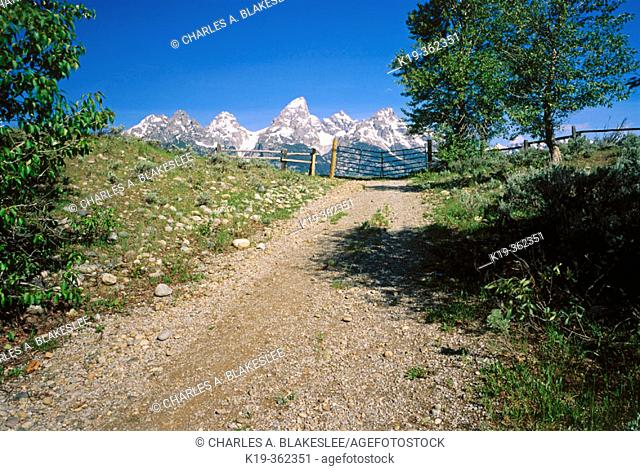 Gravel road and gate, Teton Mountain Range, Grand Teton National Park. Teton County, Wyoming. USA