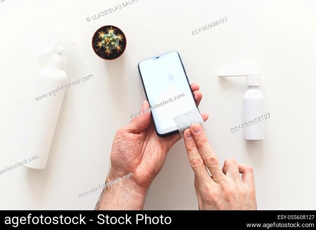 Man disinfects smartphone wiping by antibacterial wipe to prevent yourself from coronavirus COVID-19. Flat lay, on white