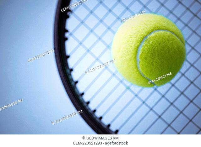 Close-up of a tennis ball and a tennis racket
