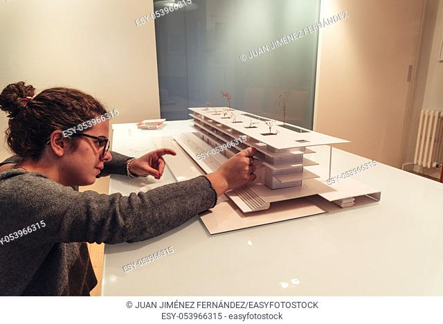 Female architect working on architecture model made with cardboard on table in office of architectural firm