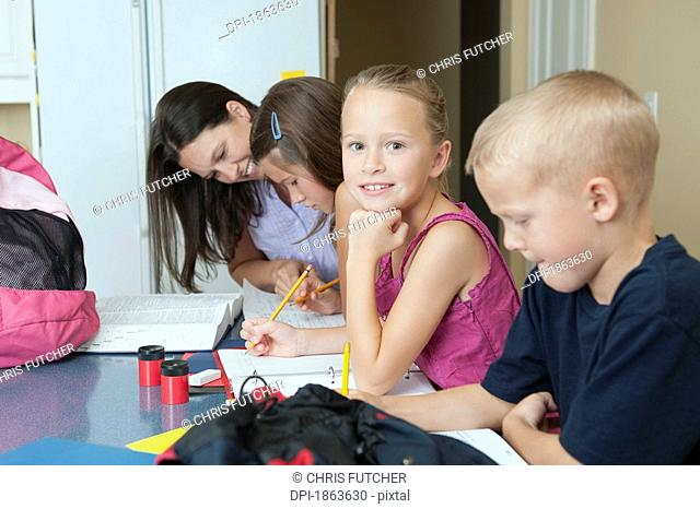 A mother helping her children with their homework