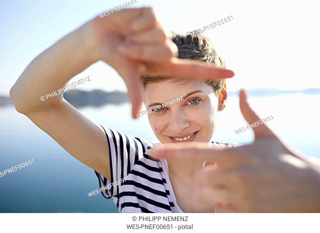 Portrait of woman in front of lake shaping frame with her fingers
