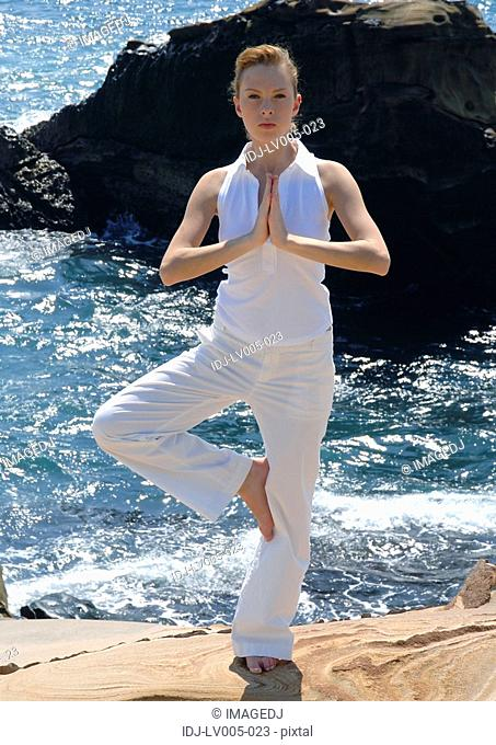 Portrait of a young woman practicing yoga in the tree pose