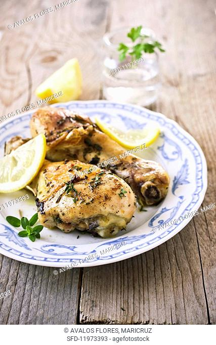 Grilled chicken legs with fresh herbs and lemons