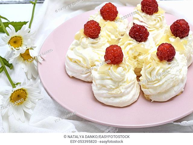 cakes made of egg white and whipped white cream with raspberries on a pink plate, Pavlova dessert