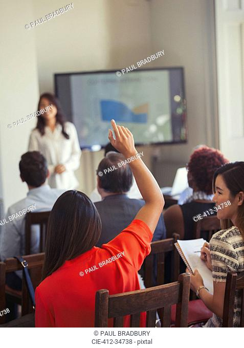Businesswoman in audience asking question at business conference
