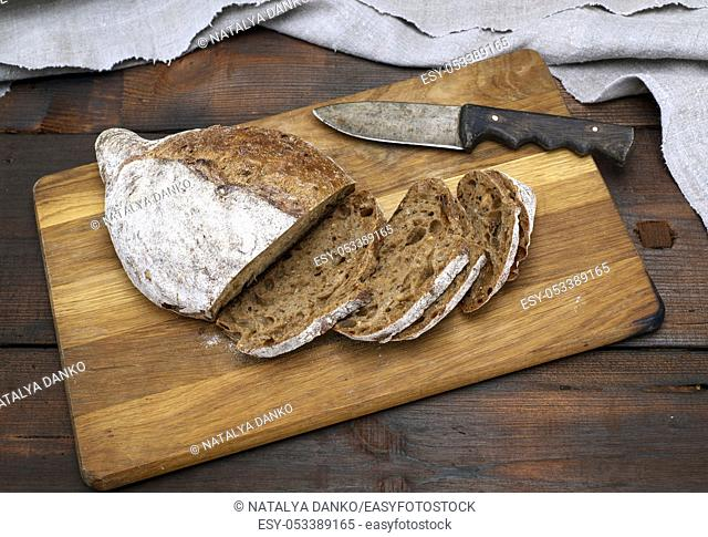 sliced bread with rye flour flour on a brown wooden board, top view